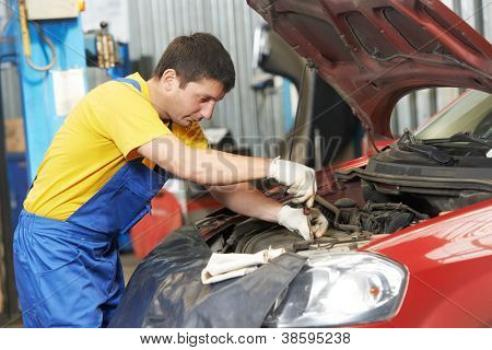 One young auto mechanic tighten screw with spanner during automobile car maintenance at engine repair service station