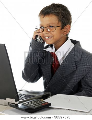 A young elementary boy delightedly talking on the phone behind his computer while wearing his dad's business suit.  On a white background.