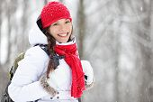 Woman winter hiking. Beautiful young Asian woman enjoying the falling snow dressed in a cheerful red