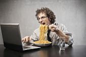 Man gorging of spaghetti with tomato sauce using a laptop computer