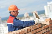 stock photo of masonic  - construction mason worker bricklayer installing red brick with trowel putty knife outdoors - JPG