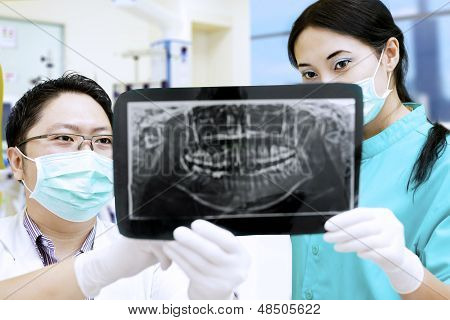 Dentist And Assistant Analysing X-ray At Dental Clinic