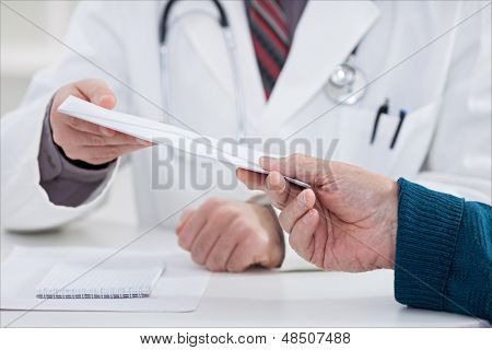 patient bribing doctor, giving money in envelope