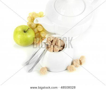 Unrefined sugar in white sugar bowl on grey background