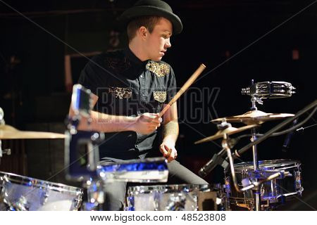 Handsome man in hat and black shirt plays drum set in night club.