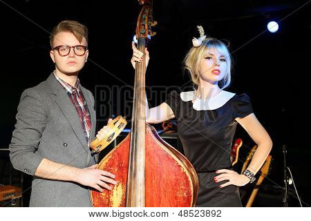 Man in glasses with tambourine and woman in black dress with contrabass in night club.