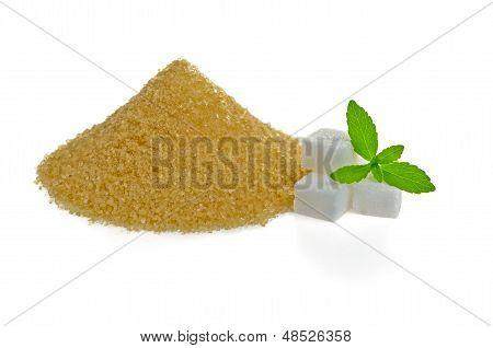 Stevia leaves with sugar cubes and a brown sugar heap