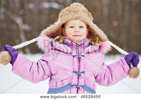 Half-length portrait of smiling little girl in pinky jacket with fur collar who stretches to sides drawstrings of her earflapped hat in winter park