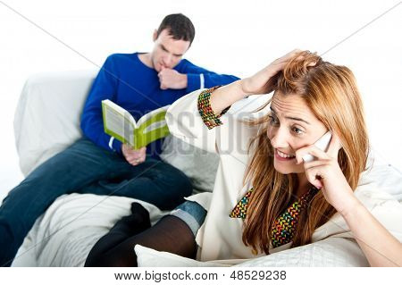 Woman chatting on a mobile whilst a man reads in the background