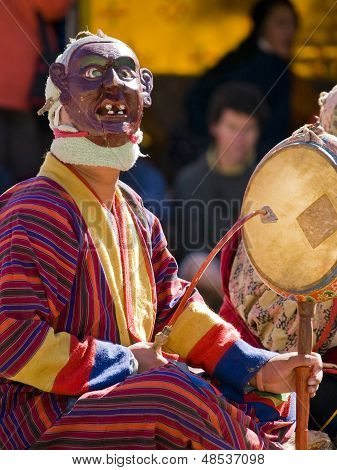 Masked man making music during a tsechus (Bhutanese festival) in Bumthang, Bhutan