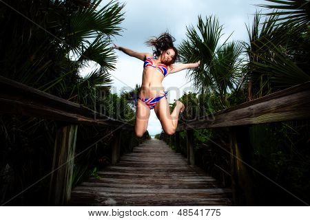 Young Brunette woman in a bikini on a beach boardwalk