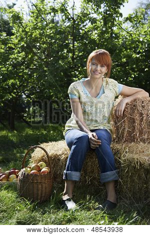 Full length portrait of a young woman sitting on hay bales near orchard