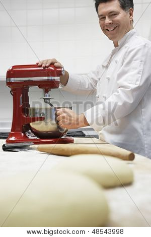 Side view of a smiling male chef using dough mixer in kitchen with focus on dough in foreground