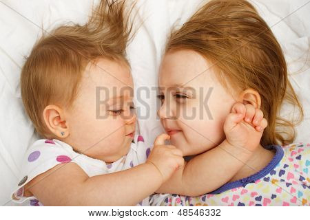 Siblings cuddling in bed