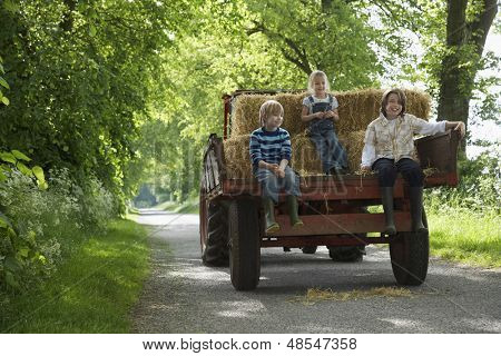 Full length portrait of three young kids sitting on back of trailer on country lane