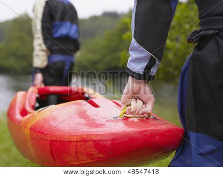 Rear view of two men carrying red kayak to river