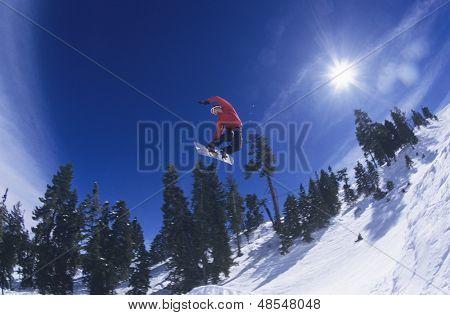 Low angle view of a person on snowboard jumping over snowed landscape