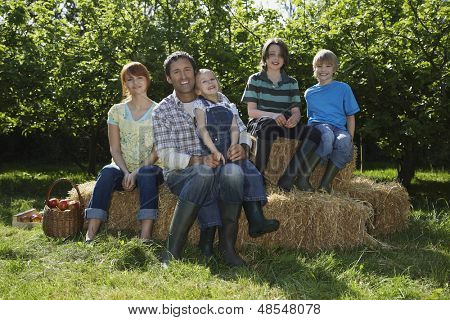 Full length portrait of parents with three children sitting on hay bales near orchard