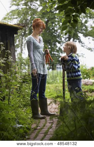 Full length side view of smiling mother and son with spade in the garden