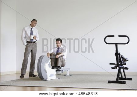 Businessman using rowing machine with colleague standing by