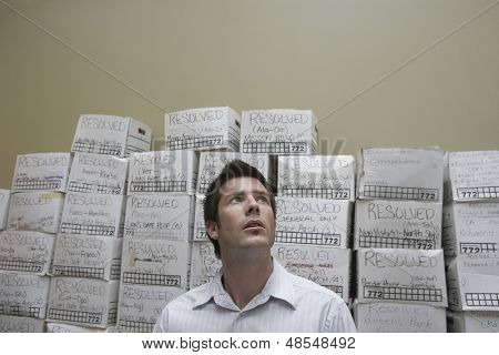 Businessman in front of stack of filing boxes in storage room