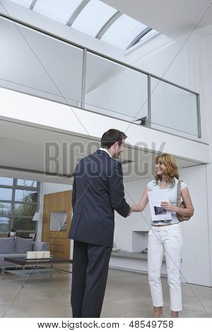 Male real estate agent shaking happy woman's hand in new home