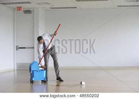 Full length of a middle aged businessman using mop in empty room