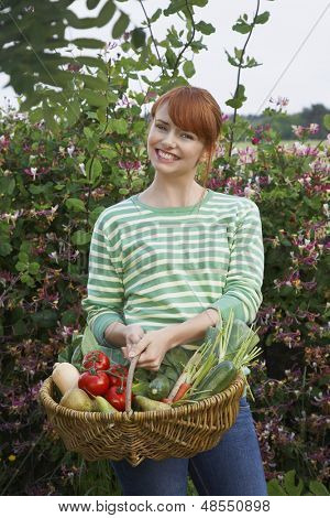 Portrait of a smiling young woman holding vegetable basket in garden