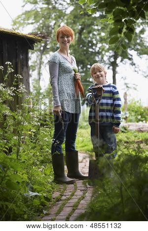 Full length of smiling mother and son with spade in the garden