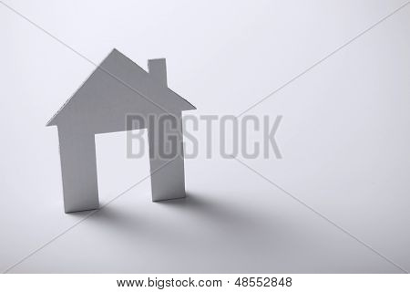 business and real estate concept - white paper house over white background