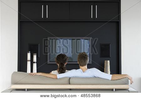 Rear view of young couple watching TV together in living room