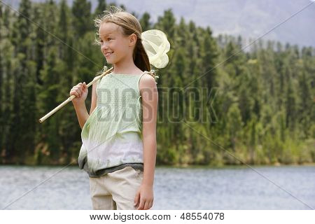 Happy young girl with butterfly net standing by lake
