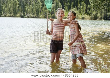 Portrait of happy young girls holding fishing nets in lake