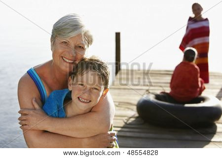 Portrait of happy senior woman hugging grandson on jetty with sisters in background