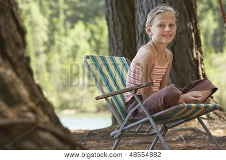 Portrait of happy young girl sitting on deckchair in forest