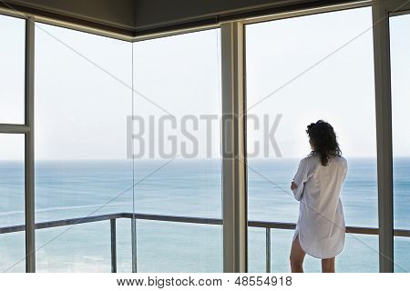 Rear view of young woman looking at ocean view from balcony at resort