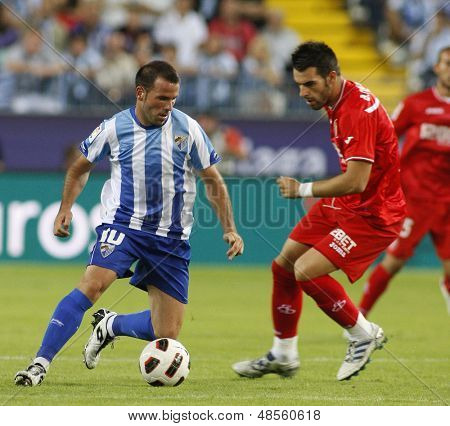 MALAGA, SPAIN. 19/09/2010. Apo�?�?�?�±o the Malaga midfielder is watched by �?�?�?�lvaro Negredo a Sevilla forward player during the La Liga match between CF Malaga and Sevilla, played in the La Rosaleda Stadium