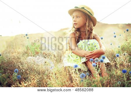 Kid girl resting in summer field