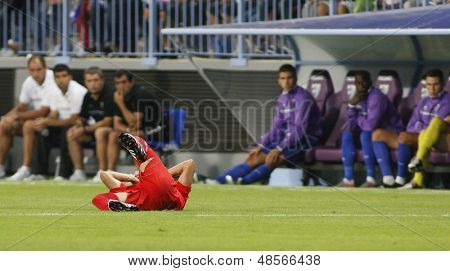 MALAGA, SPAIN. 19/09/2010.  A Sevilla player rolls on the floor injured and watched by the Malaga team bench during the La Liga match between CF Malaga and Sevilla, played in the La Rosaleda Stadium