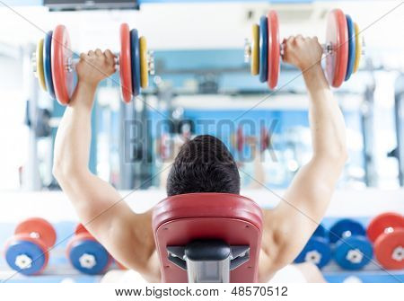 Strong handsome man lifting heavy free weights at the gym