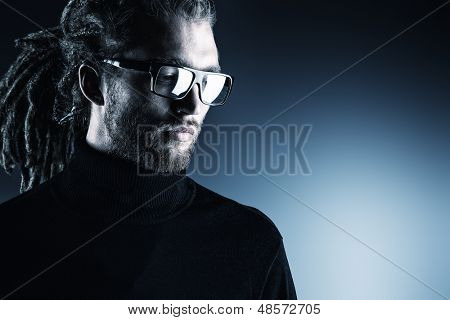 Portrait of a modern handsome young man in spectacles over dark background.