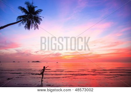 Silhouette young woman in a jump on the sea beach at sunset (concept of long-awaited vacation)