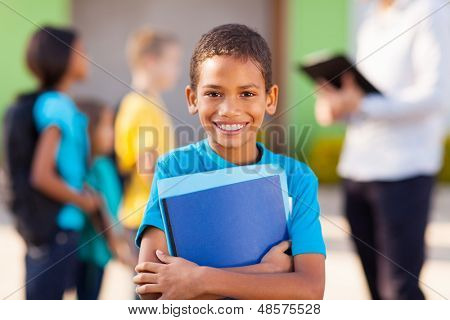 cheerful african male elementary school student holding text books