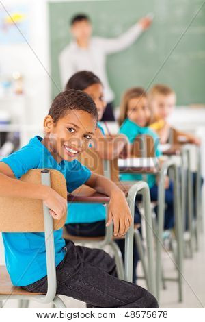 smiling elementary school boy in classroom looking back