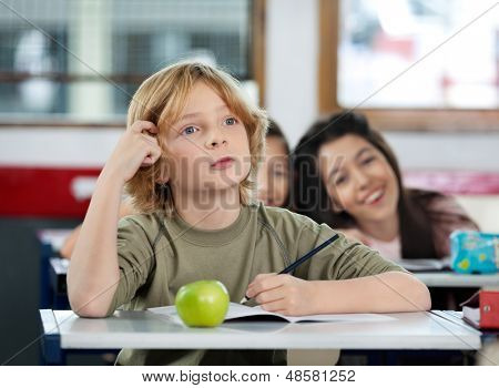 Thoughtful schoolboy scratching his head while looking away at desk in classroom