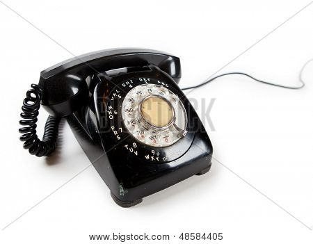 Old Late 60s - 70s style black telephone with rotary dial. Isolated on white. Cable extending in to the white background.