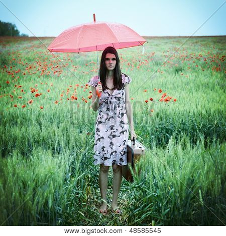 Young beautiful woman with umbrella and suitcase walking on a poppy field, summer outdoor.