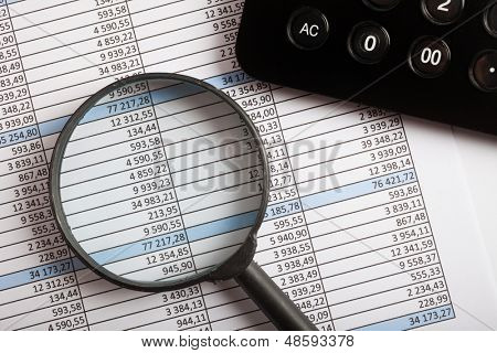 Calculator and magnifying glass over a business document