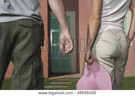 Closeup rear view midsection of man and woman in front of house with keys and hat