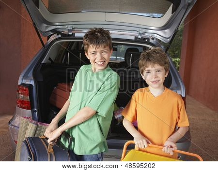 Portrait of two smiling boys carrying suitcases in front of car